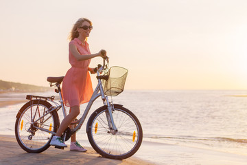 Fashionable young woman with bicycle on the beach at sunset