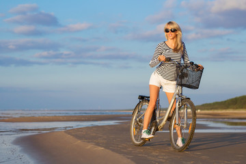 Young woman riding bicycle on the beach