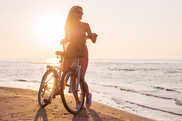 Vintage fashioned woman with bicycle on the beach