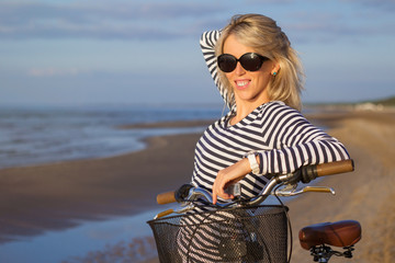 Portrait of trendy young woman with bicycle on the beach