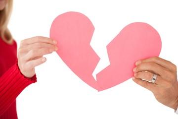 Hands holding two halves of broken heart