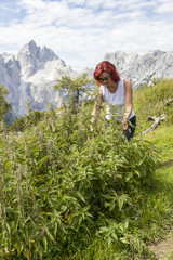 Cute smiling woman picking stinging nettle leaves