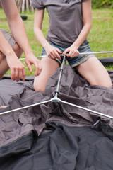 młodzi ludzie rozkładają namiot na kempingu w słoneczny dzień