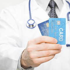Doctor holding two credit cards in his hand - 1 to 1 ratio