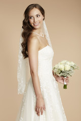 Beautiful young bride in wedding dress holding bouquet.