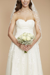 Close up of bride in wedding dress holding bouquet.
