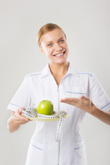 Smiling woman doctor with a green apple and measuring tape.