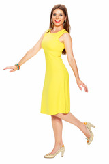 Fashionable young woman in yellow dress posing on white backgro