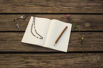 Open notebook, wooden pencil and chaplet on wooden background