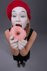 Portrait of pretty female mime eating a tasty pink donut isolate