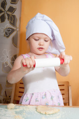 baby girl in cook role on kitchen