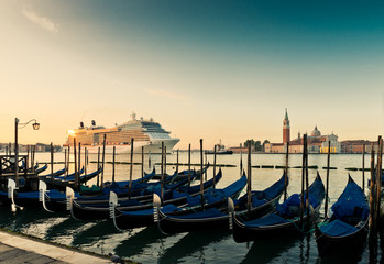 Gondolas on the background of the huge cruise ship in Venice's G