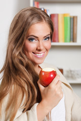 Portrait of a beautiful young woman eating apple