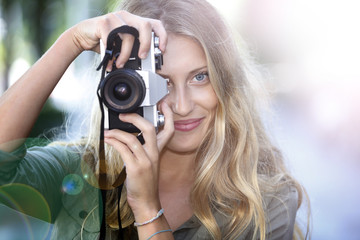 Beautiful cheerful girl using vintage photo camera