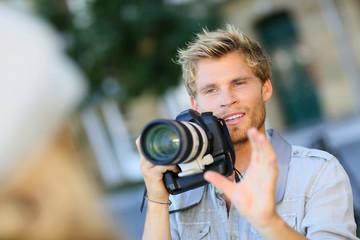 Young photographer shooting model outside