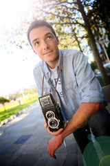 Young man holding vintage camera