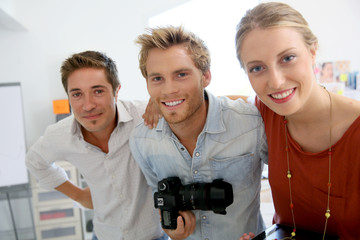 Portrait of cheerful creative team in photo agency