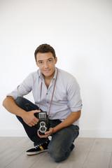 Smiling photographer holding vintage camera