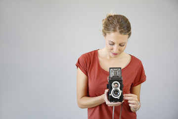 Cheerful girl with vintage camera on grey background