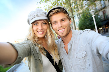 Cheerful trendy couple taking self-portrait picture