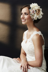 Glamorous young bride in wedding dress, smiling.