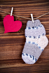 Baby Sock with red Heart on Wood