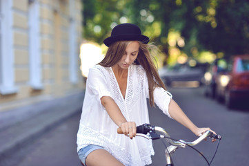Young lady on a vintage bike outdoor portrait