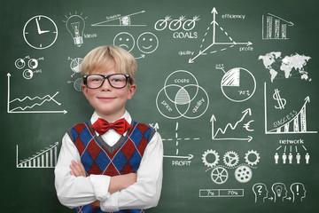 Kind vor Tafel mit Business-Symbolen