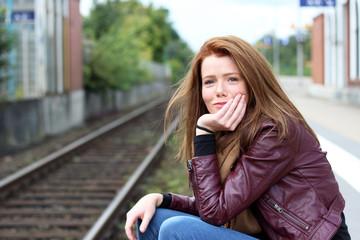 junge, freundliche Frau sitzt am Bahnhof
