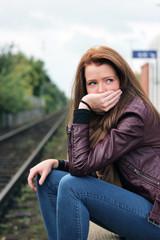 einsame, junge Frau sitzt an den Gleisen