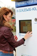junge Frau bedient Fahrkartenautomat