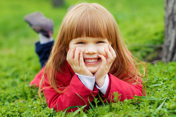 happy smiling little girl with red hair laying on a grass