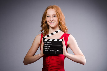 Woman in red dress with movie board