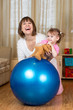 mother and kid play with fitness ball home