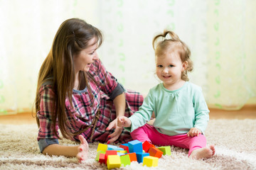 happy mom and kid play toys at home