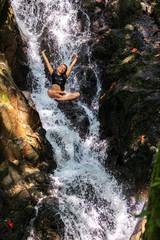 Beautiful woman sitting in natural waterfall