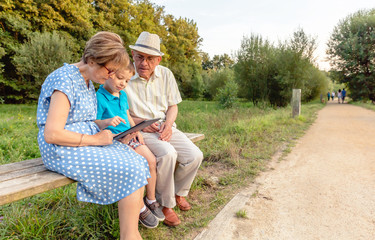 Grandchild and grandparents using a tablet outdoors