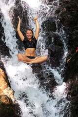 Young woman enjoying in natural tropical Waterfall