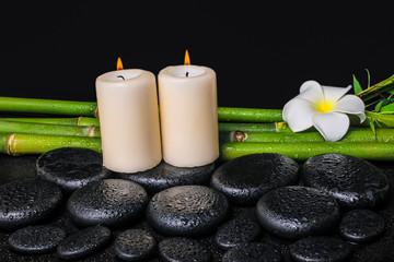 spa concept of zen basalt stones, white flower plumeria, candles