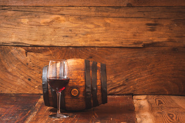 Red wine in a glass with a bottle and barrel on wooden rustic ta