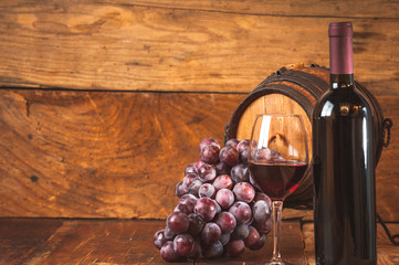 Red grapes and a bottle of wine and barrel on wooden rustic tabl