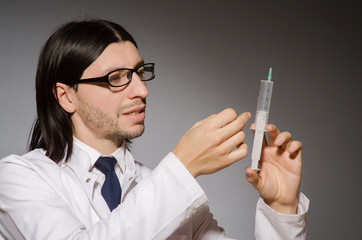 Young doctor man with  syringe against grey background