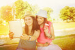 Leinwanddruck Bild - Two pretty young women in park taking a selfie with tablet