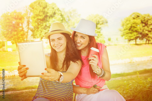 Leinwanddruck Bild Two pretty young women in park taking a selfie with tablet