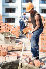 Bricklayer worker cutting brick with masonry hammer