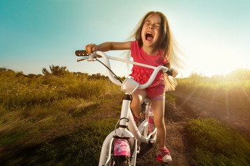 Portrait of happy funny girl on bicycle