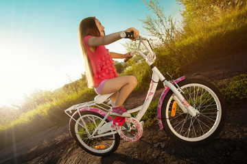Happy little girl riding a bicycle