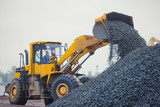 Yellow heavy excavator and bulldozer unloading road metal during - 70368390