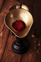 saffron spice in antique vintage iron scale bowl on wooden table