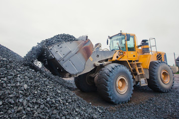 Yellow heavy excavator and bulldozer unloading road metal during